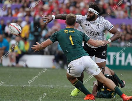 Stock Photo of Heino Bezuidenhout, Semi Kunatani. Fiji's Semi Kunatani, right, is tackled by South Africa's Heino Bezuidenhout during their semifinal match at the Hong Kong Sevens rugby tournament in Hong Kong