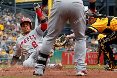 Yunel Escobar, Chris Stewart. Los Angeles Angels' Yunel Escobar (6) slides safely past the tag of Pittsburgh Pirates catcher Chris Stewart, right, on a sacrifice fly to right field by Albert Pujols during the first inning of a baseball game in Pittsburgh