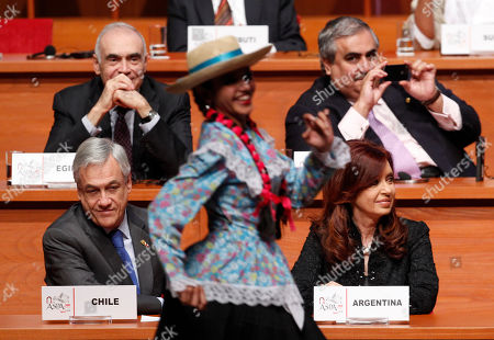 Mohammed Kamel Amr, Sheikh Khalid bin Ahmed Al Khalifa, Sebastian Pinera, Cristina Fernandez. A traditional dancer performs in front of Egyptian Foreign Minister Mohammed Kamel Amr, top left, Bahrain's Foreign Minister Sheikh Khalid bin Ahmed Al Khalifa, top right, Chile's President Sebastian Pinera, bottom left, and Argentina's President Cristina Fernandez during day two of a summit with heads of state and governments of South American and Arab Countries, in Lima, Peru