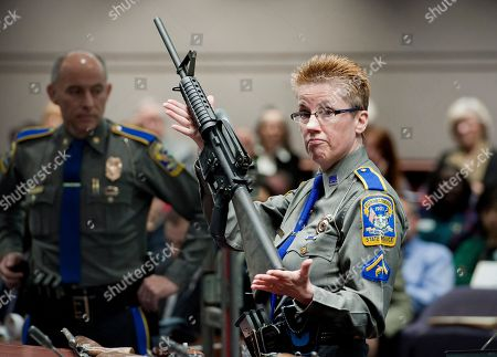 Firearms Training Unit Detective Barbara J. Mattson of the Connecticut State Police holds up a Bushmaster AR-15 rifle, the same make and model of gun used by Adam Lanza in the Sandy Hook School shooting, for a demonstration during a hearing of a legislative subcommittee reviewing gun laws, at the Legislative Office Building in Hartford, Conn., . The parents of children killed in the Newtown school shooting called for better enforcement of gun laws Monday at the legislative hearing