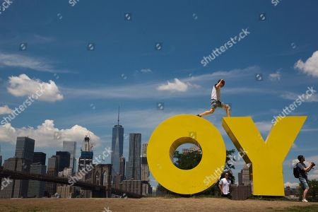 A visitor to the Brooklyn Bridge park jumps between the letters in Deborah Kass' sculpture OY/YO, in New York