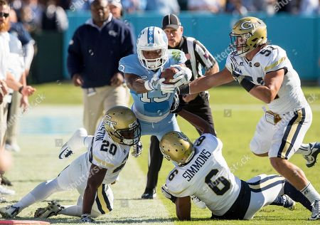 Bug Howard, Lawrence Austin, Lamont Simmons, Brant Mitchell. North Carolina's Bug Howard (13) attempts to stretch for a first down as Georgia Tech's Lawrence Austin (20), Lamont Simmons (6), and Brant Mitchell (51) defend during the first half of an NCAA college football game Chapel Hill, N.C