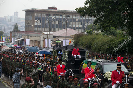 A procession of soldiers on foot and on horseback accompany the body of late Prime Minister Meles Zenawi as it arrives at Holy Trinity Cathedral for burial in Addis Ababa, Ethiopia . Thousands of mourners gathered in a public square in Ethiopia's capital on Sunday to pay their final respects to Zenawi, who was praised for lifting many out of poverty but vilified by some for restricting freedoms. Zenawi, who ruled for 21 years, died Aug. 20 of an undisclosed illness in a Belgian hospital. He was 57