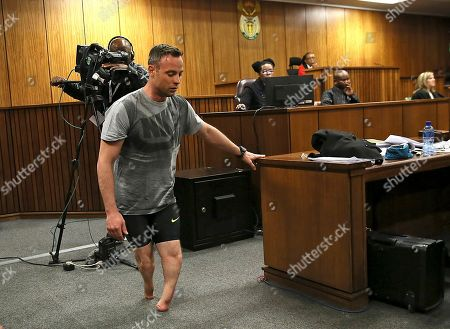 Oscar Pistorius walks on his stumps during argument in mitigation of sentence by his defense attorney Barry Roux in the High Court in Pretoria, South Africa, . An appeals court found Pistorius guilty of murder and not a lesser charge of culpable homicide for the shooting death of his girlfriend Reeva Steenkamp