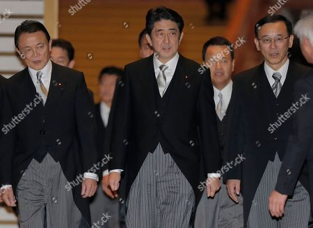 Shinzo Abe, Taro Aso, Sadakazu Tanigaki. Japan's new Prime Minister Shinzo Abe, center, Finance and Deputy Prime Minister Taro Aso, left, Justice Minister Sadakazu Tanigaki, right, walk with other Cabinet members for a group photo session after attending an attestation ceremony for his Cabinet at the Imperial Palace in Tokyo . Old-guard veteran Abe was voted back into office as prime minister Wednesday and immediately named a new Cabinet, ending three years of liberal administrations and restoring power to his conservative, pro-big-business party that has run Japan for most of the post-World War II era