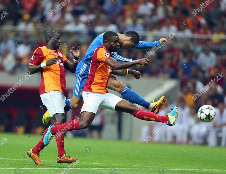 Emmanuel Eboue of Galatasaray, left, watches as Real Madrid's Cristiano Ronaldo, background centre, vies for the ball with Galatasaray's Aurelien Chedjou, during their Champions League Group B soccer match, in Istanbul, Turkey