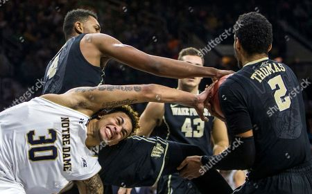 Zach Auguste, Doral Moore, Devin Thomas. Notre Dame's Zach Auguste (30) reacts as he has the ball stolen by Wake Forest's Doral Moore (4) and Devin Thomas (2) during the second half of an NCAA college basketball game, in South Bend, Ind