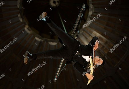 Stock Picture of Violinist Shenzo Gregorio performs while strapped into a trapeze in the Queen Victoria Building in Sydney, . Gregorio plays to shoppers on three levels while he is suspended up to 25 meters (82 feet) in the air