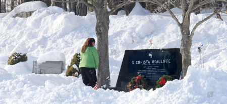 Stock Image of Former Concord High School student Kelly Garfield, who had Christa McAuliffe as a homeroom teacher, stands, in Concord, N.H., at her gravesite at 11:38, 25-years after the shuttle Challenger exploded, killing McAuliffe and the rest of the crew