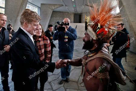 Chief of the Huli tribe in Papua New-Guinea, Mundiya Kepanga, right, shakes hand with American actor and environmental activist Robert Redford, prior to a conference on climate, at the UNESCO headquarters, in Paris, . Negotiators adopted a draft climate agreement Saturday that was cluttered with brackets and competing options, leaving ministers with the job of untangling key sticking points in what is envisioned to become a lasting, universal pact to fight global warming