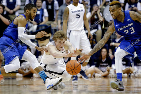 J.P. Macura, James Milliken, Maurice Watson Jr. Xavier's J.P. Macura, center, dives for a loose ball against Creighton's James Milliken (23) and Maurice Watson Jr., left, during the second half of an NCAA college basketball game, in Cincinnati. Xavier won 98-93