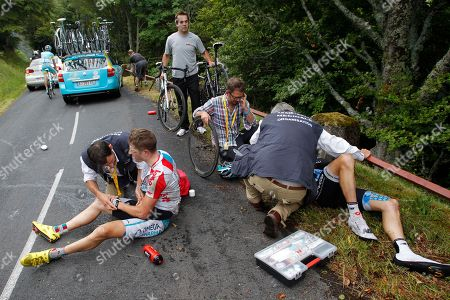 Frederik Willems of Belgium, left, and David Zabriskie of the US, right, are being treated by Tour de France doctors after crashing during the 9th stage of the Tour de France cycling race over 208 kilometers (129 miles) starting in Issoire and finishing in Saint Flour, central France