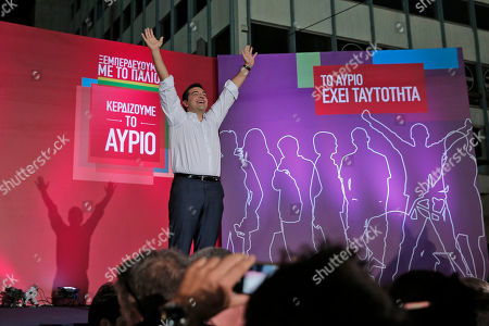 Syriza left-wing party leader and former Prime Minister Alexis Tsipras waves to his supporters before his speech at a pre-election rally in Athens, . Opinion polls indicate a race too close to call, with Tsipras struggling to maintain the narrowest of leads over his main opponent, center-right New Democracy leader Evangelos Meimarakis. The banner, left, reads in Greek: 'We get rid of the old', and 'We win tomorrow' while the one on the right reads: 'Tomorrow has identity