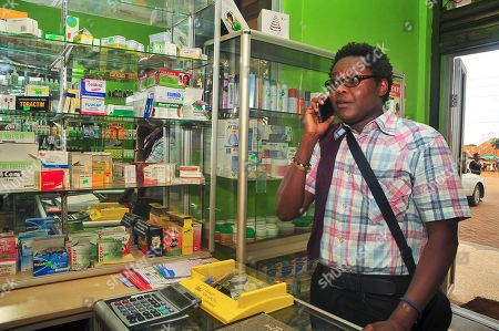 Stock Photo of Prominent gay rights activist and Sexual Minorities Uganda program coordinator Pepe Julian Onziema makes a phone call while in a pharmacy in the suburbs of Kampala, Uganda . Uganda's health minister said Wednesday that gays will not be discriminated against by medical workers after the country's president signed a law that strengthens criminal penalties against homosexuals, but prominent gay rights activist Pepe Julian Onziema said that well-known homosexuals face constant discrimination and abuse and recalled being ignored many times by medical workers who served others as they gossiped about his sexual orientation
