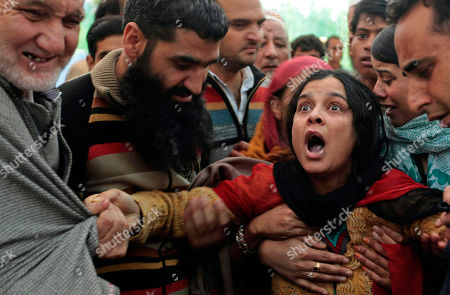 The daughter-in-law of Haji Syed Mohammad Yousuf, a 61-year-old retired teacher and worker of the governing National Conference party in Indian-controlled Kashmir, wails during his funeral procession in Locktipora, some 55 Kilometers (34 miles) south of Srinagar, India, . Yousuf died in police custody Friday after the disputed region's top elected official handed him over to investigators for probing charges that he took money from people promising to get them nominated as lawmakers, according to news reports