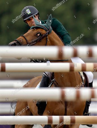 Stock Picture of Wilexo, ridden by Carlos Motta Ribas, of Brazil, turns away from jumping a pole during the equestrian individual show jumping competition at the 2012 Summer Olympics, in London