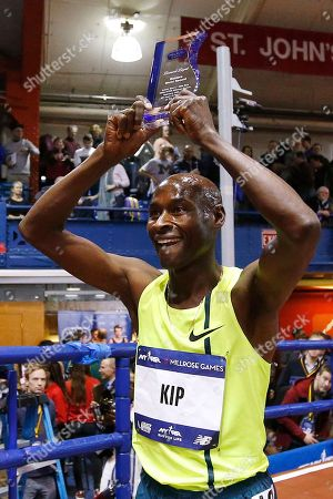 Bernard Lagat holds up his world record trophy as he celebrates after breaking the world record for men over 40, in the men's Wanamaker Mile during the Millrose Games track and field meet, in New York. Lagat finished fourth with a time of 3 minutes, 54.91 seconds