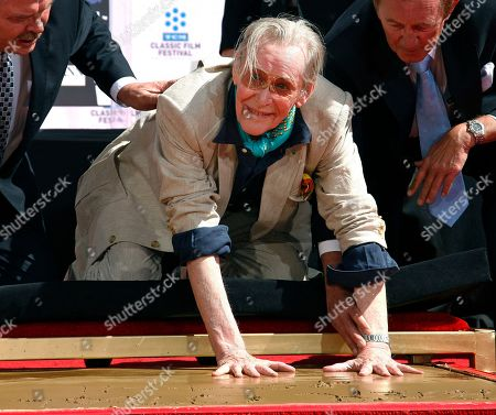Actor Peter O'Toole places his handprints in cement as he is honored during the TCM Classic Film Festival at Grauman's Chinese Theatre, in Los Angeles