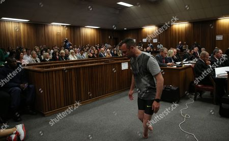 Oscar Pistorius, walks on his stumps during argument in mitigation of sentence by his defense attorney Barry Roux in the High Court in Pretoria, South Africa, . An appeals court found Pistorius guilty of murder and not a lesser charge of culpable homicide for the shooting death of his girlfriend Reeva Steenkamp