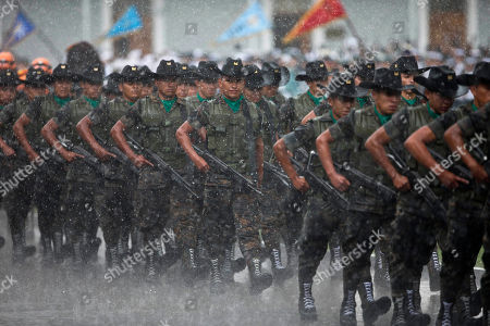 Soldiers march in the rain during a military ceremony recognizing Guatemala's new President Alejandro Maldonado as the commander-in-chief in Guatemala City, . Shortly after taking the oath of office Thursday, Maldonado demanded that ministers and top officials submit their resignations so he could form a transition government and promised an honest and inclusive administration. Maldonado replaces Otto Perez Molina who resigned late Wednesday amid a corruption scandal