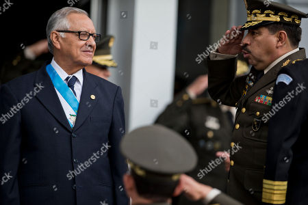 Guatemala's new President Alejandro Maldonado, left, is saluted by Military Chief of Staff Alfredo Sosa during a military ceremony recognizing him as the new commander-in-chief in Guatemala City, . The conservative former judge will serve out the term of former President Otto Perez Molina, who resigned late Wednesday after a judge issued an order for this detention. Prosecutors accuse the ex-president of leading a customs fraud ring