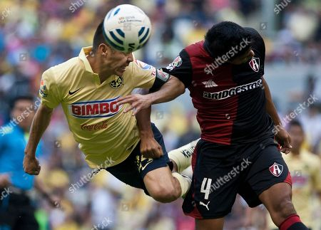 Oribe Peralta, Luis Venegas. America's Oribe Peralta, left, heads the ball against Luis Venegas of Atlas during a Mexican soccer league match in Mexico City
