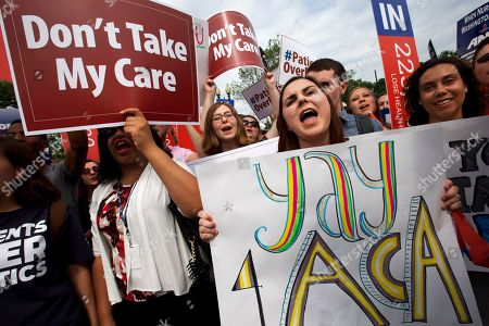 """Jessica Ellis, right, holds a sign that says """"yay 4 ACA,"""" as she and other supporters of the Affordable Care Act react with cheers as the opinion for health care is reported outside of the Supreme Court in Washington, in Washington"""