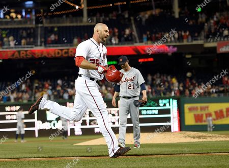 Washington Nationals' Clint Robinson (25) rounds the bases and heads home after he hit a walk off home run during the ninth inning of an interleague baseball game as Detroit Tigers relief pitcher Mark Lowe (21) is at back, in Washington. The Nationals won 5-4