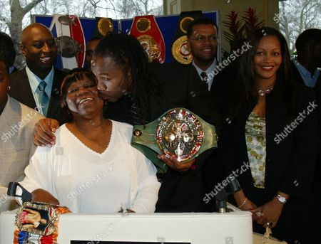 Stock Image of Lennox Lewis Press Conference.  Grosvenor Hotel.  Lennox Lewis With His Mother Violet.  Lewis Looked Pensive As He Announnced His Retiremet Before Taking Comfort From A Bunch Of Violets - His Mum And Fiancee.