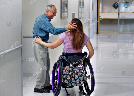 Olympic swimmer Amy Van Dyken-Rouen talks with Craig Hospital Director of Phychology Dr. Lester Butt before leaving the hospital in Englewood, Colo., . Van Dyken-Rouen was left paralyzed just below the waist in an all-terrain vehicle crash on June 6 in Arizona