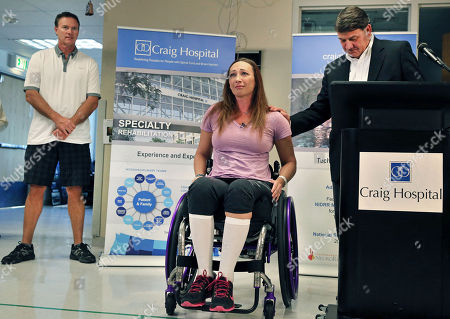 Olympic swimmer Amy Van Dyken-Rouen, center, flanked by Craig Hospital CEO Mike Fordyce, right, and her husband Tom Rouen, left, talks with members of the media about inspirational staff and fellow patients on the day of her discharge from Craig Hospital, in Englewood, Colo., . Van Dyken-Rouen was left paralyzed just below the waist in an all-terrain vehicle crash on June 6 in Arizona