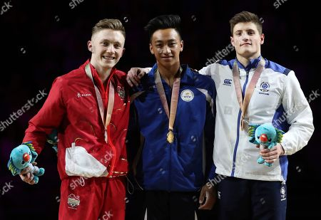 Marios Georgiou, Nile Wilson, Frank Baines. Men's parallel bars gold medalist Cyprus' Marios Georgiou, centre, stands with silver medalist Nile Wilson of England, left, and bronze medalist Scotland's Frank Baines, right, during the medal ceremony at the artistic gymnastics competition at the Commonwealth Games at Coomera Indoor Stadium on the Gold Coast, Australia
