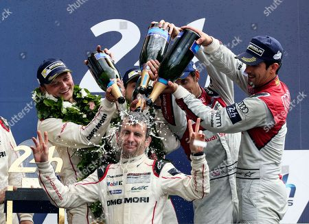 The Porsche 919 Hybrid No2 of the Porsche Team driven by Neel Jani of Switzerland, Romain Dumas of France, Marc Lieb of Germany and Coach driver Jeromy Moore celebrate with champagne, after winning the 84th 24-hour Le Mans endurance race, in Le Mans, western France