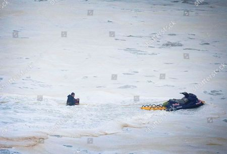 Brazilian surfer Carlos Burle, left, rescues fellow surfer Maya Gabeira, also from Brazil who nearly drowned after falling trying to ride a big wave at the Praia do Norte, north beach, at the fishing village of Nazare in Portugal's Atlantic coast . Gabeira was taken to hospital and is reportedly doing well despite suffering a broken ankle