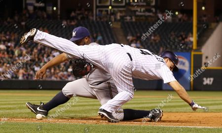 Nick Hundley, Jason Rogers. Colorado Rockies' Nick Hundley, front, collides with Milwaukee Brewers first baseman Jason Rogers as he picks up the ball after fielding a slow roller hit by Hundley in the ninth inning of a baseball game, in Denver. Hundley was called out on the play. Milwaukee won 9-5
