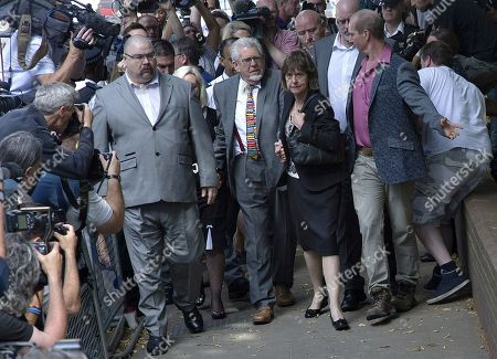 Veteran entertainer Rolf Harris, center, accompanied by his niece Jenny, center right, and daughter Bindi, centre left, arrives at Southwark Crown Court to be sentenced, in London, . Australian-born Harris has been sentenced to five years and nine months in prison for a string of abuses against young girls