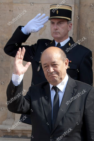 France's new Defense Minister, Jean-Yves Le Drian, bids farewell to France's outgoing Defense Minister Gerard Longuet during the handover ceremony in Paris