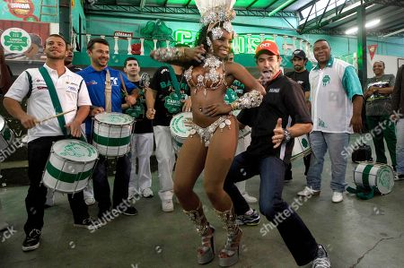 IndyCar driver Helio Castroneves, of Brazil, front right, dances with a samba dancer as other IndyCar drivers, Oriol Servia, of Spain, second from left, and E.J. Viso, of Venezuela, left, play drums at a samba school in Sao Paulo, Brazil, . Brazil will host the 4th race of the IndyCar season on May 1