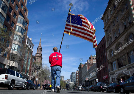 Lt. Mike Murphy of the Newton, Mass., fire dept., carries an American flag down the middle of Boylston Street after observing a moment of silence in honor of the victims of the bombing at the Boston Marathon near the race finish line, in Boston, Mass. At 2:50 p.m., exactly one week after the bombings, many bowed their heads and cried at the makeshift memorial on Boylston Street, three blocks from the site of the explosions, where bouquets of flowers, handwritten messages, and used running shoes were piled on the sidewalk