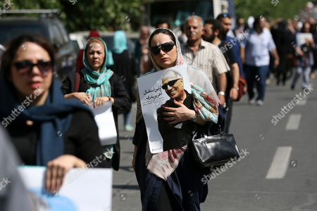 "A woman holds a poster of Iranian film director Abbas Kiarostami at his funeral ceremony in Tehran, Iran, . Kiarostami who died on Monday in Paris, where he was undergoing treatment for cancer at the age of 76 after a career spanning more than four decades. He wrote and directed dozens of films. His 1997 film ""Taste of Cherry"" won the prestigious Palme d'Or at the Cannes Film Festival. The poster reads in Persian: "" The first welcoming, the last farewell"
