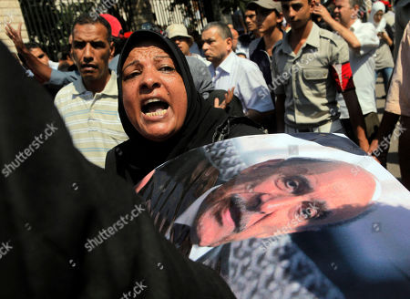 An Egyptian woman grieves during the military funeral honoring Egypt's former spy chief Omar Suleiman, seen in the poster at right, in Cairo, Egypt, . The 76-year-old Suleiman died Thursday in a U.S. hospital. The shadowy statesman was considered Mubarak's most trusted man, handing the regime's most sensitive issues like relations with the U.S. and Israel and the fierce battle against Islamists
