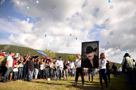 A couple carry a framed portrait of Mexican ballad singer Joan Sebastian through the cemetery in Juliantla, Mexico, . Sebastian, one of Mexico's great ballad singers, died on July 13. He was 64. After five days of homage and farewells by thousands of fans, Sebastian was laid to rest in his hometown's cemetery