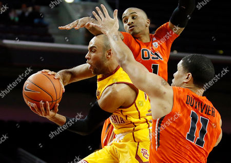Julian Jacobs, Gary Payton II, Malcolm Duvivier. Southern California's Julian Jacobs, left, passes off the ball as he jumps between Oregon State's Gary Payton II, rear, and Malcolm Duvivier, right, during the second half of an NCAA college basketball game, in Los Angeles. Southern Cal won 81-70