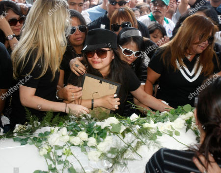 """Charice Pempengco, Raquel Pempengco. Filipino singer Charice Pempengco, third from right, of the TV hit """"Glee"""", cries during interment of her estranged father Ricky Pempengco at a memorial park at Cabuyao township, Laguna province south of Manila, Philippines. Ricky Pempengco was stabbed to death in nearby San Pedro township early this week by Angel Capili Jr. who later surrendered to police and admitted his crime. At right is Charice's mother Raquel"""