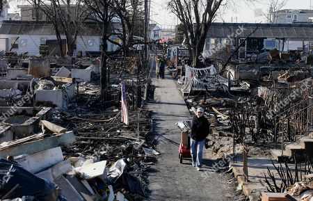 Louise McCarthy carts belongings from her flood-damaged home as she passes the charred ruins of other homes in the Breezy Point section of the Queens borough of New York, . A fire destroyed more than 100 homes in the oceanfront community during Superstorm Sandy