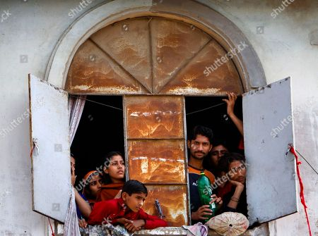 A family look funeral procession of Pakistani slain politician Imran Farooq through a window of their house in Karachi, Pakistan on . Thousands of mourners attended the funeral Saturday of the Pakistani politician who was stabbed in London in September in a slaying that set off rioting in his hometown of Karachi