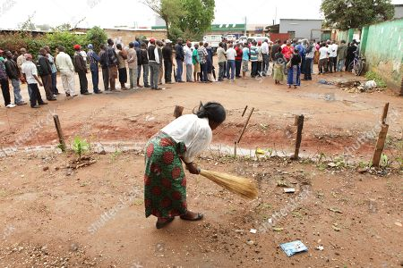 A woman sweeps outside her house as people queue at a nearby polling station during presidential election day in Lusaka, . Zambians are voting to choose a new leader following the death of Michael Sata, 77, who died Oct. 2014, in a London hospital following a long illness, after serving as President of the Southern African country since 2011