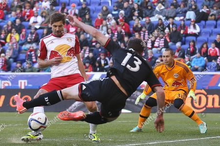 Damien Perrinelle, Luis Robles, Chris Pontius. New York Red Bulls defender Damien Perrinelle, left, blocks a shot by D.C. United forward Chris Pontius (13) as Red Bulls goalkeeper Luis Robles (31) looks on during the first half of an MLS soccer game, in Harrison, N.J
