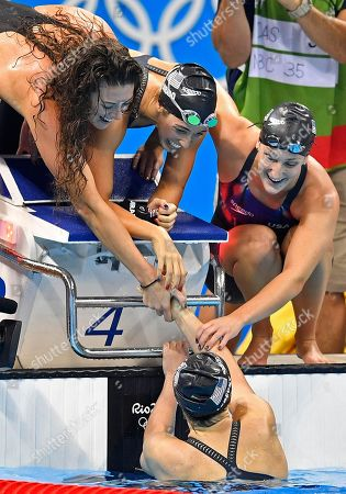 United States' Katie Ledecky, bottom shakes hand with her teammates Allison Schmitt, Maya DiRado and Leah Smith, from left, during the women's 4 x 200-meter freestyle relay final in the swimming competitions at the 2016 Summer Olympics, in Rio de Janeiro, Brazil