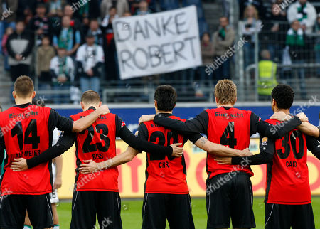 Frankfurt's players pay a minute of silence for late goal keeper Robert Enke prior to the German first division Bundesliga soccer match between Eintracht Frankfurt and Borussia Moenchengladbach in Frankfurt, central Germany, on . Background reads:' Thanks Robert